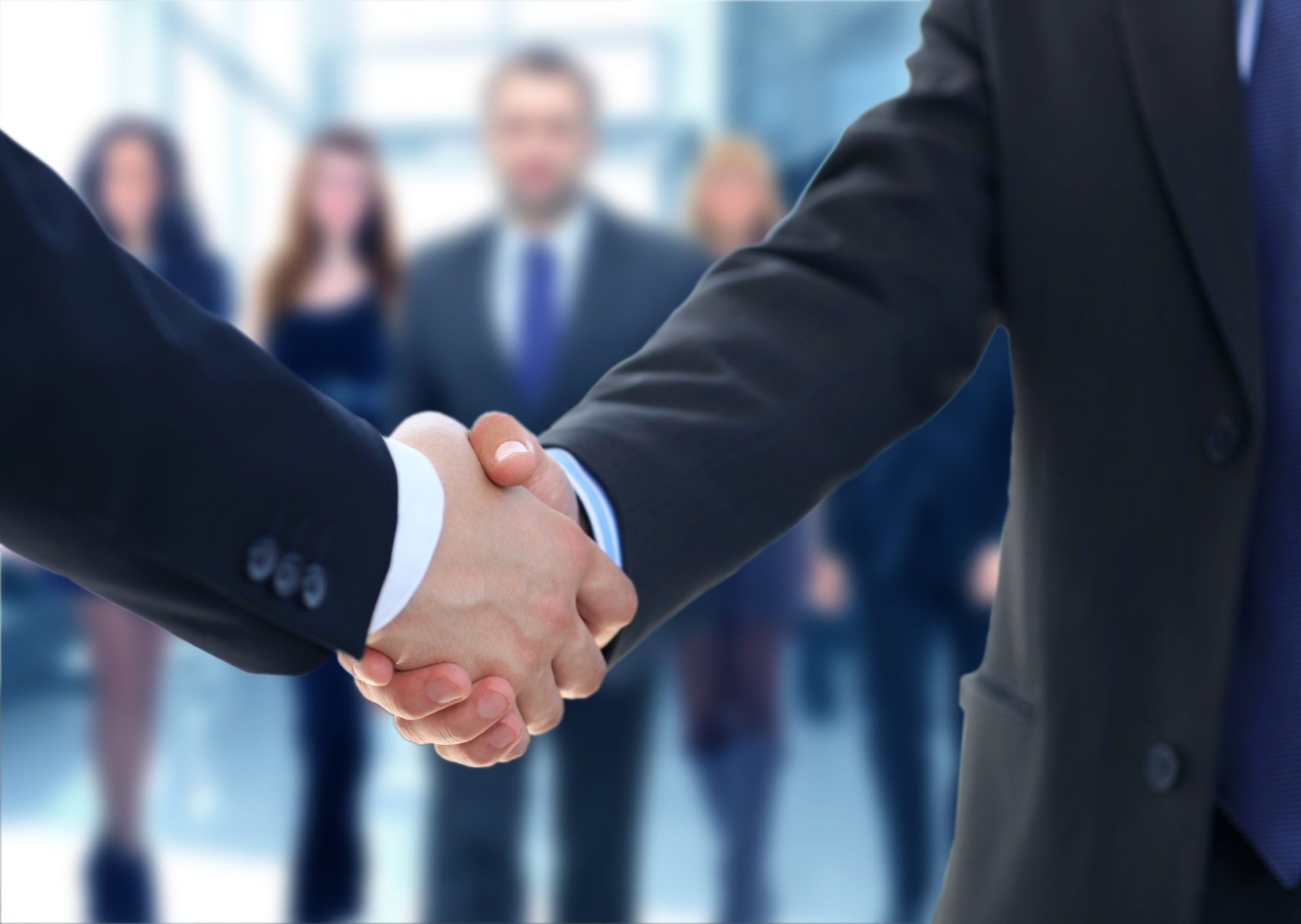 Representative of a Canadian Sales Organization closing a deal with a handshake